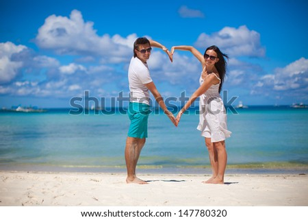 Young couple enjoying each other on a tropical beach and making heart with hands