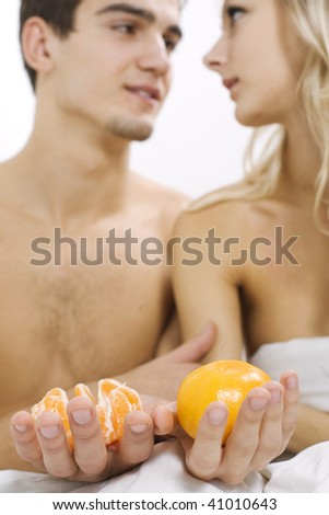 Young couple enjoying fruit breakfast in bed - stock photo