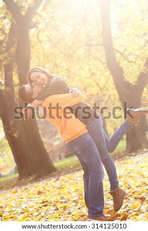 Young couple enjoying in the autumn day. Boyfriend hugging a girlfriend and kissing her on the cheek. - stock photo