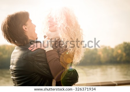 Young couple enjoying life together outdoor - man lifting and holding woman - stock photo