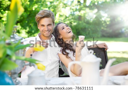 Young couple enjoying lunch in the garden - stock photo