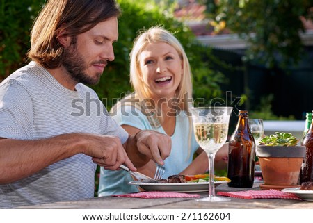 young couple enjoying lunch with white wine outdoors in garden - stock photo