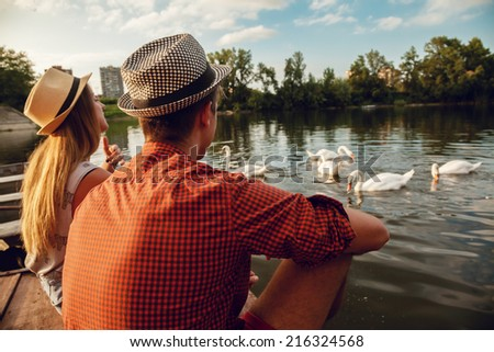 Young Couple Enjoying Near River With Swans Around - stock photo