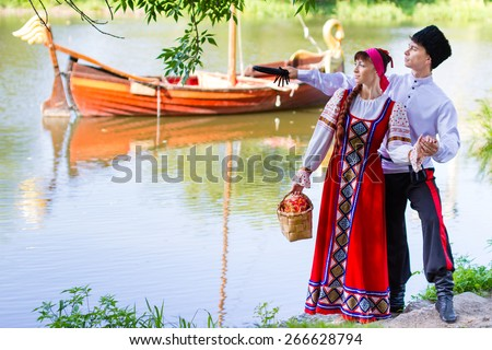 Young couple enjoying picnic near the river - stock photo
