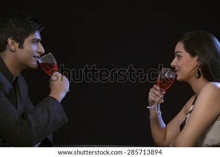 Young couple enjoying red wine on romantic date - stock photo