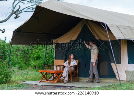 Young couple enjoying safari trip in front of their tent - stock photo
