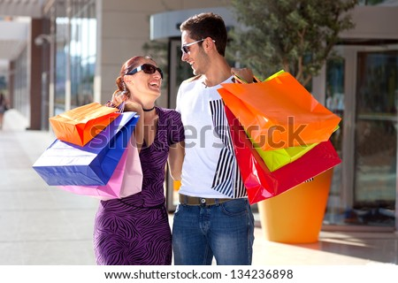 Young couple enjoying shopping. Happy young couple embracing each other, having fun during shopping, carrying colorful shopping bags - stock photo