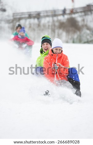 Young couple enjoying sled ride on snow covered slope - stock photo