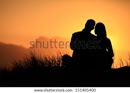 Young couple enjoying the sunset on the beach.  - stock photo