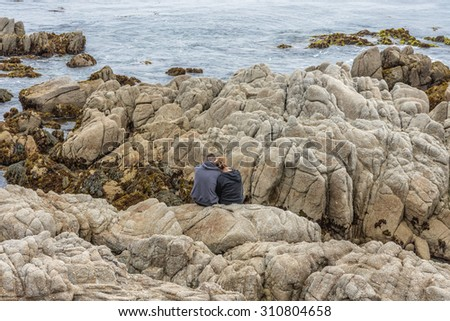 Young couple enjoying the view along the rugged Big Sur coastline, near Monterey, CA. on the California Central Coast.