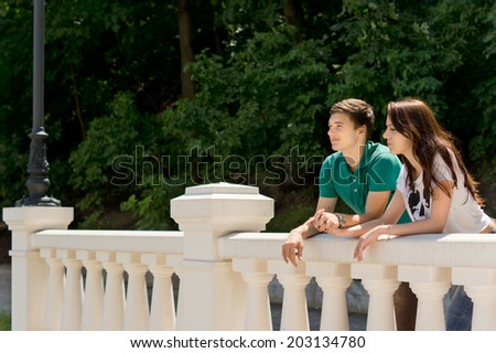 Young couple enjoying the view from a bridge standing in the summer sunshine holding hands and smiling against leafy greenery - stock photo