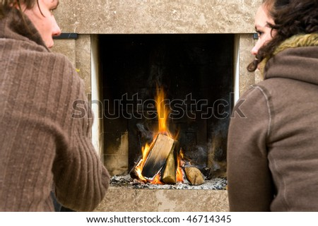 Young couple enjoying the warmth of a fire. Focus on the fireplace - stock photo