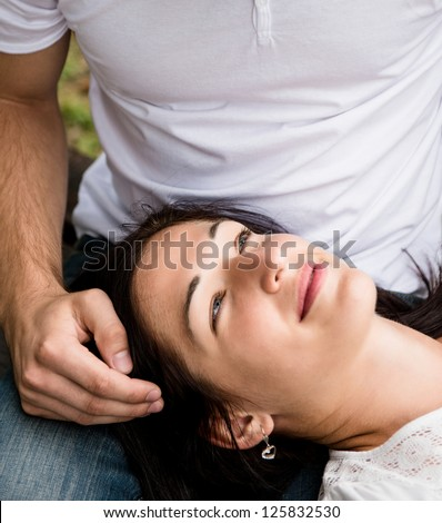 Young couple enjoying time together - woman lying on knees of man