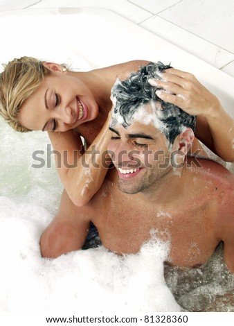 Young couple enjoying together in a jacuzzi. Young woman applying shampoo to a man. - stock photo