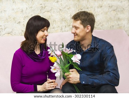 Young couple European on dating, man presents bouquet flowers to woman. - stock photo