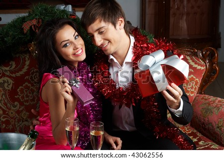Young couple exchanging gifts on a New Year celebration - stock photo