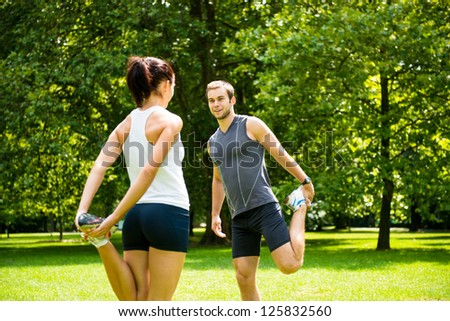 Young couple exercising and stretching muscles before sport activity - outdoor in nature