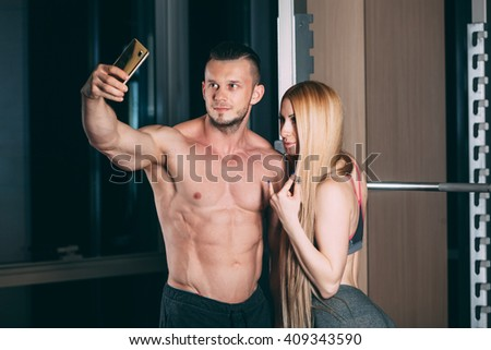 Young couple exercising in gym with weights  man, selfie, Snapshots on the phone. - stock photo