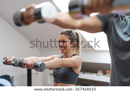 Young couple exercising with dumbbells at home.  - stock photo