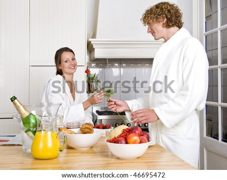 Young couple expressing their love at a valentines champagne breakfast - stock photo