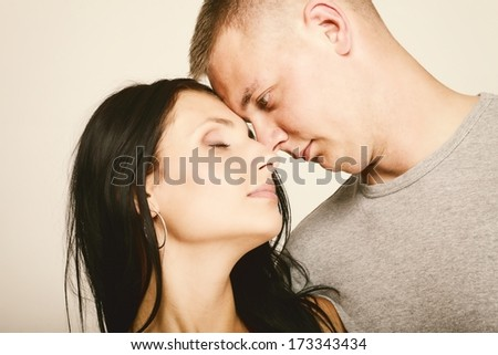 Young couple, face to face, in a loving pose.
