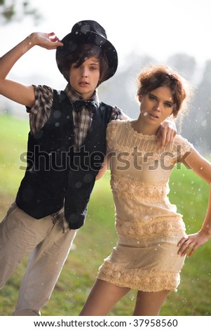 Young couple fashion. Standing at the rain. - stock photo