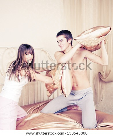 Young couple fighting pillows in the bedroom - stock photo