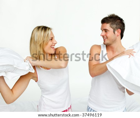 Young couple fighting with pillows in bed - stock photo