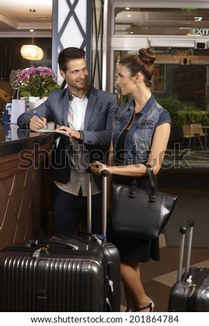 Young couple filling in check in form at hotel reception upon arrival, smiling happy. - stock photo