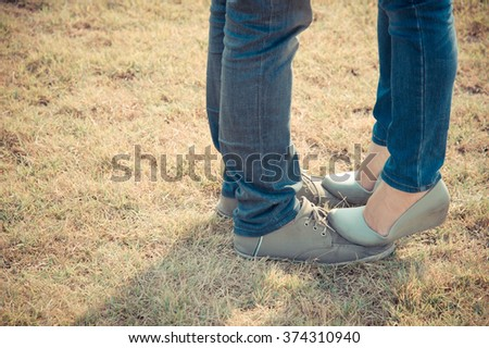 Young couple first kiss in summer warm weather.Young couple in love standing in garden.  - stock photo