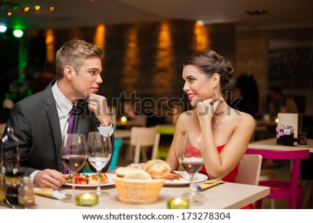 Young couple flirting in restaurant - stock photo