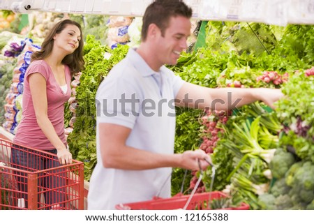 Young couple flirting in supermarket aisle