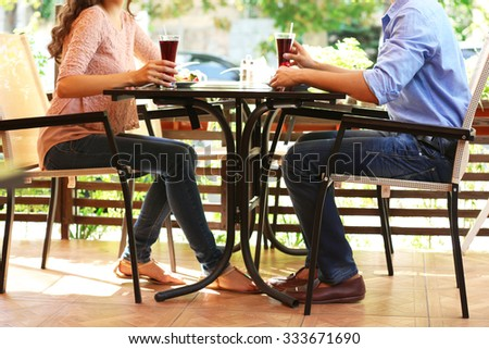 young couple flirting on cafe's summer terrace - stock photo