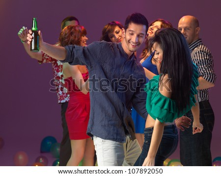 young couple flirting on the dancefloor in a night club - stock photo