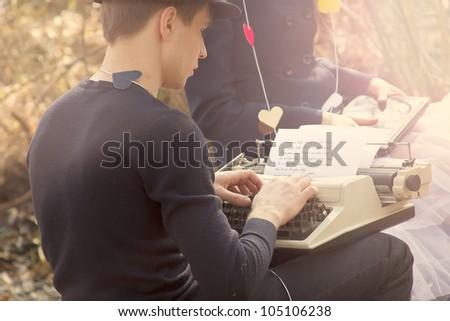 Young couple freelance typing on an old typewriter in the square - stock photo