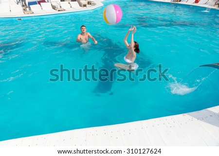 Young couple frolicking in a turquoise blue swimming pool throwing a colorful beach ball to each other - stock photo
