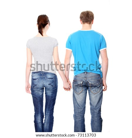 Young couple from behind, holding hands - stock photo