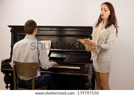Young couple giving a classical duet with an attractive stylish young woman singing from a music score accompanied by a young man on a piano - stock photo