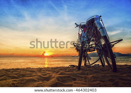 Young couple go to the beach to see the sunset and leave their bicycles on the beach in Nha Trang
