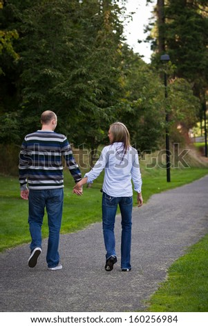 young couple going on an afternoon walk in the park