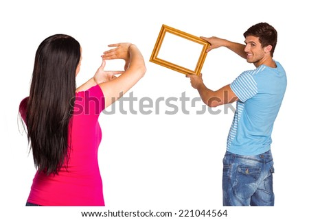 Young couple hanging a frame on white background - stock photo