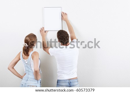 Young couple hangs framed on the wall - stock photo