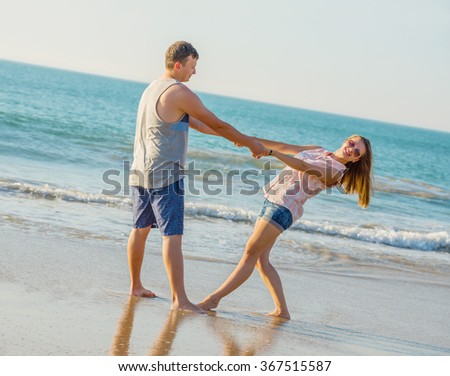 Young couple have fun  on the beach  at sunset