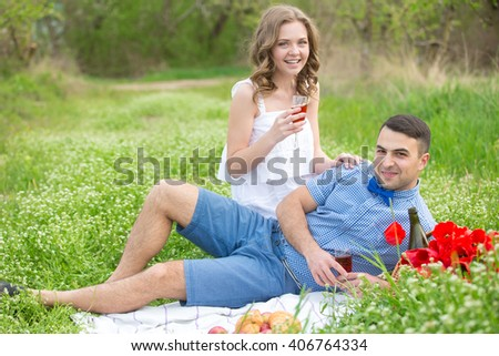 Young couple have picnic with red wine on the summer meadow
