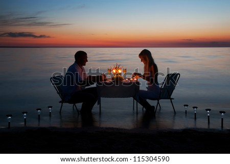 Young couple have romantic evening with candles on sea beach - stock photo