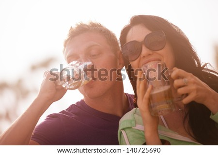 Young couple Having a Beer at Sunset at the beach in Venice California - stock photo