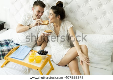 Young couple having a breakfast in the bed - stock photo