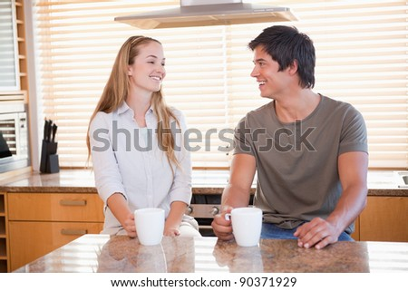 Young couple having a cup of coffee in their kitchen - stock photo