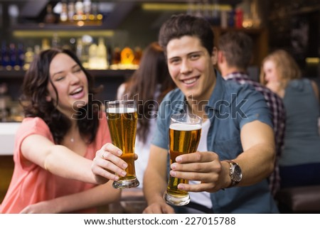 Young couple having a drink together at the bar - stock photo