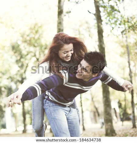 Young couple having a good time together at the park (selective focus with shallow DOF) - stock photo